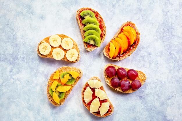 Torradas de café da manhã saudável com manteiga de amendoim, geléia de morango, frutas