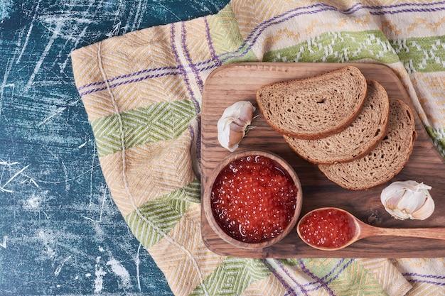 Torradas de caviar vermelho na placa de madeira.