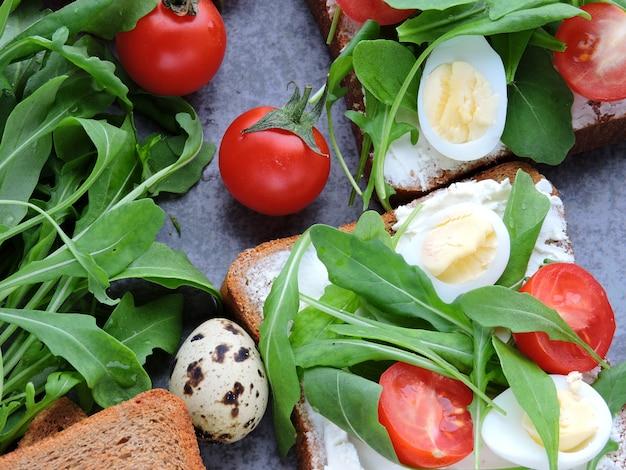 Torradas de centeio com rúcula, ovos de codorna e tomate cereja.