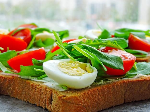 Torradas de fitness com rúcula, queijo creme, tomate cereja e ovos de codorna