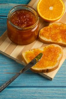 Torradas de pão com confiture de laranja em tábua de madeira