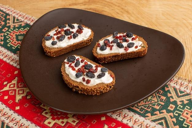 Torradas de pão com frutas secas em prato escuro sobre mesa de madeira