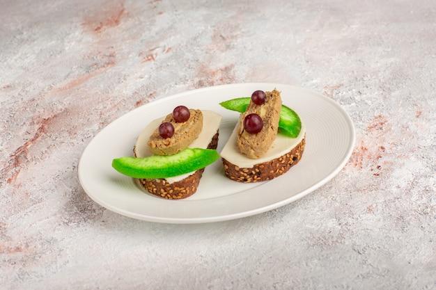 Torradas de pão com patê e fatias de pepino em um prato na mesa branca