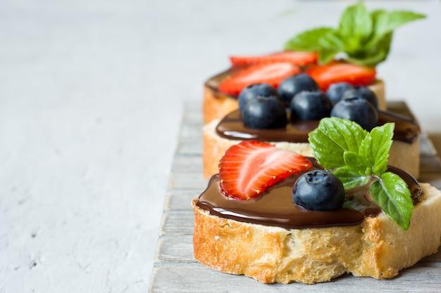 Torradas de pão com propagação de chocolate e frutas morangos mirtilos hortelã em um suporte de mesa de madeira cinza