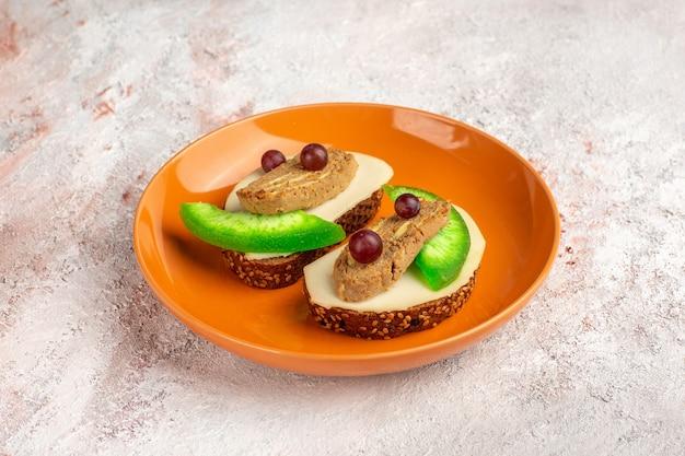 Torradas de pão de vista frontal com patê e fatias de pepino dentro de um prato de laranja na superfície branca