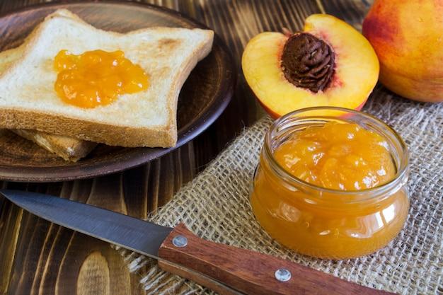 Torradas de pão, geléia de nectarina e frutas no fundo de madeira marrom