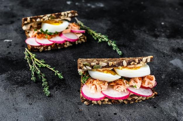 Torradas de pão integral com salmão defumado quente, ovo e rabanete.