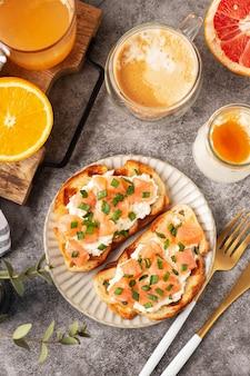 Torradas de queijo e salmão, conceito de café da manhã com café e suco de laranja espremido na hora, comida saudável.