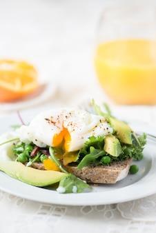 Torradas e ovo escaldado com salada verde, abacate e ervilhas