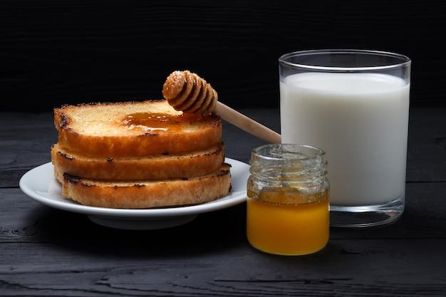 Torradas em um prato branco, um copo de leite e um pote de mel com uma colher de mel