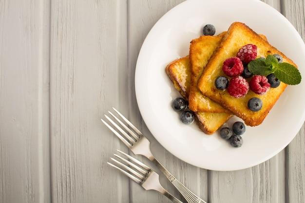 Torradas francesas com frutas e mel na chapa branca na mesa de madeira cinza. vista superior. copie o espaço.