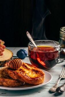 Torradas francesas com mel, frutas e chá sobre madeira branca