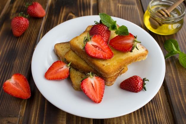 Torradas francesas com morangos e mel no prato branco