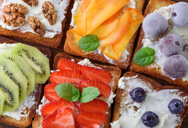 Torradas francesas com queijo macio, morangos, kiwi, nozes, cerejas e mirtilos em uma placa de madeira marrom