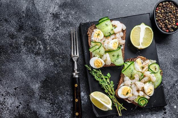 Torradas frescas com camarão, camarão, ovo de codorna e pepino no pão de centeio. fundo preto. vista do topo. copie o espaço.