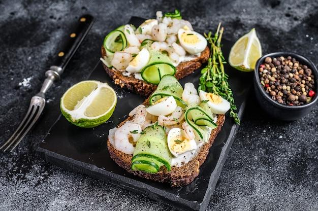 Torradas frescas com camarão, camarão, ovo de codorna e pepino no pão de centeio. fundo preto. vista do topo.