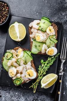 Torradas frescas com camarão, camarão, ovo de codorna e pepino no pão de centeio. vista do topo.