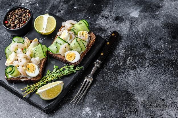 Torradas frescas com camarão, camarão, ovo de codorna e pepino no pão de centeio.