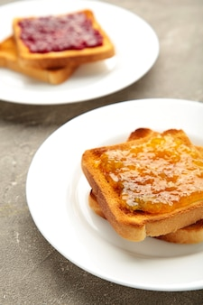 Torradas frescas com manteiga e diferentes geleias na mesa cinza. foto vertical