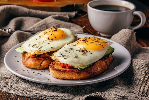 Torradas italianas com legumes e ovos fritos na chapa branca e xícara de café sobre um pano cinza áspero.
