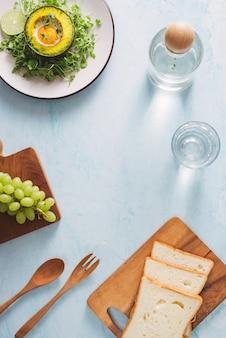 Torradas saudáveis de abacate no café da manhã ou almoço com pão, abacate fatiado, rúcula, sementes de abóbora e gergelim, sal e pimenta. sanduíches vegetarianos. dieta à base de plantas. conceito de comida inteira.