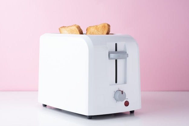 Torradeira branca com pão torrado torrado em rosa