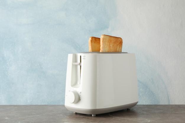 Torradeira com fatias de pão sobre fundo azul, espaço para texto