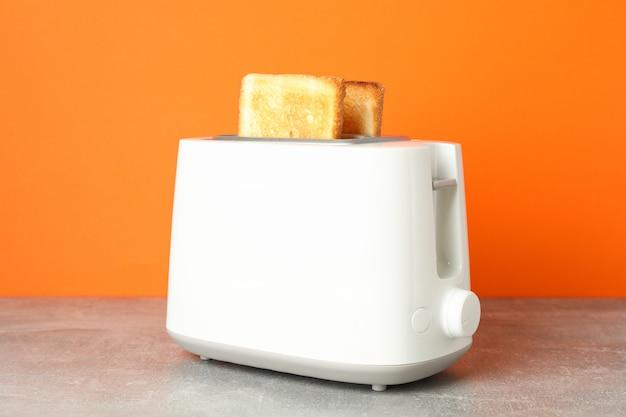 Torradeira com pão na mesa cinza contra fundo laranja, close-up