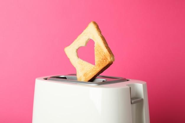 Torradeira e fatia de pão com uma forma de coração no fundo rosa, close-up