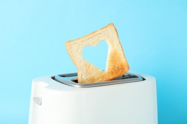 Torradeira e fatia de pão com uma forma de coração sobre fundo azul, close-up