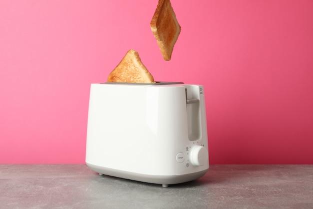 Torradeira e fatias de pão na mesa cinza contra fundo rosa, espaço para texto