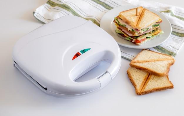 Torradeira e sanduíche fresca com queijo, ervas, tomate, pepino e bacon na mesa branca