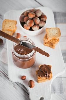Torradinhas com pasta de chocolate de avelã doce no café da manhã em uma superfície de madeira branca