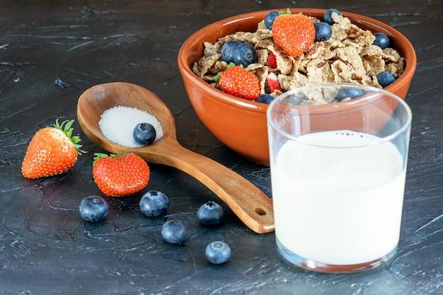 Torrado, flocos de frutas de arroz com frutas e um copo de leite sobre o fundo preto.