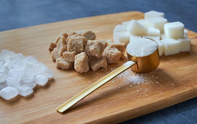 Torrão de açúcar e areia de açúcar em uma placa de madeira, close-up, profundidade rasa de nitidez