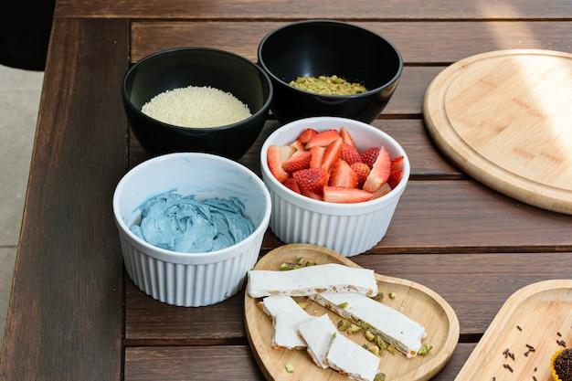 Torrão de pistache junto com ingredientes de bolo (morangos, granulado de chocolate branco, creme de manteiga azul e pistache).