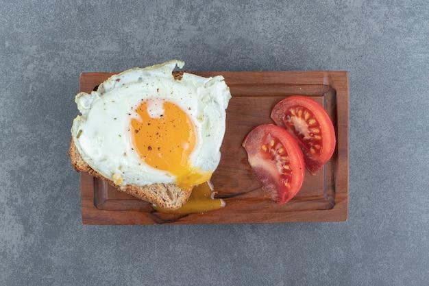 Torrar o pão com ovo frito e tomate na placa de madeira.