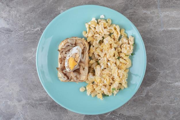 Torrar pão com ovo e macarrão na placa azul.