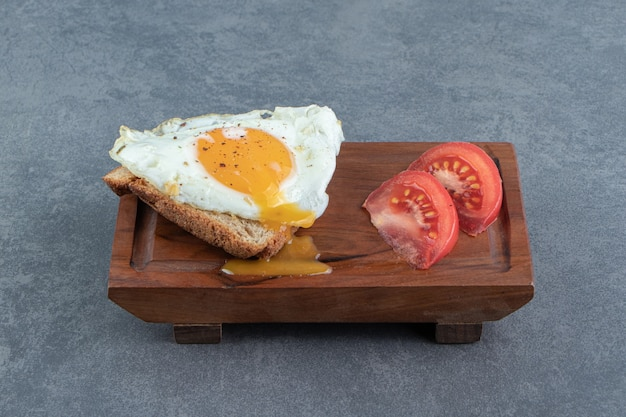 Torrar pão com ovo frito e tomate na tábua de madeira
