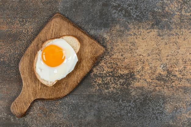 Torrar pão com ovo na tábua de madeira.
