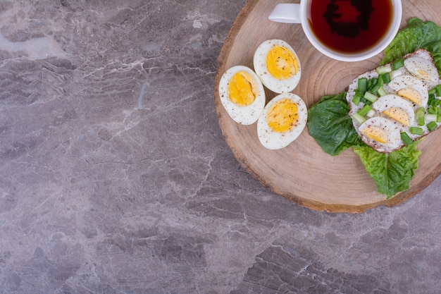 Torrar pão com ovos cozidos e ervas, servido com uma xícara de chá.