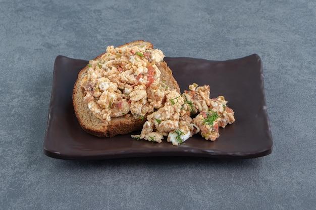 Torrar pão com salada e ovo no prato escuro.