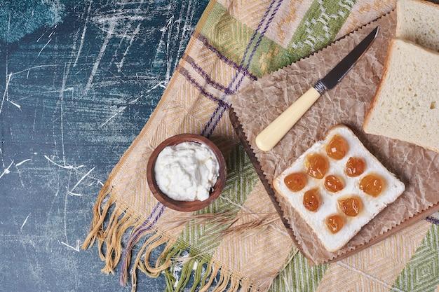 Torrar uma fatia de pão com iogurte e doce de cereja.