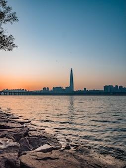 Torre com reflexo no rio.