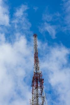 Torre da antena com céu azul e nuvens