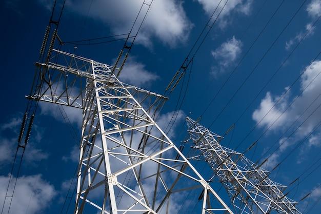 Torre da linha de energia em um fundo de céu azul com nuvens.