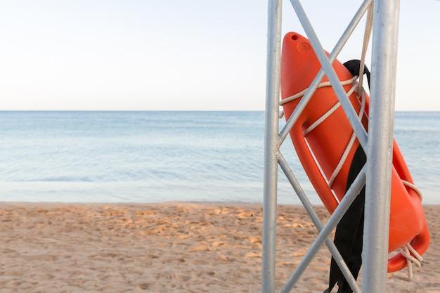 Torre da salva-vidas com a boia alaranjada na praia. bóia de resgate no poste de resgate de ferro