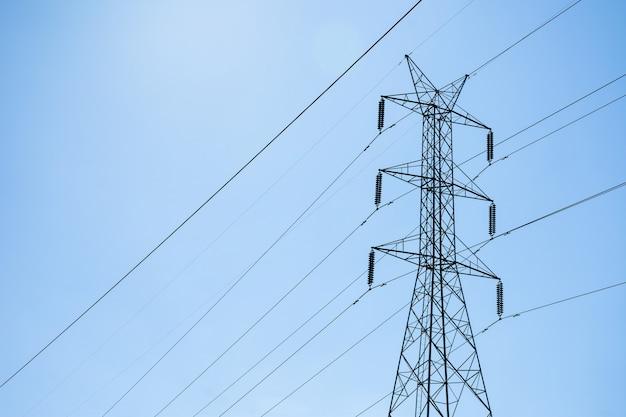 Torre de aço de energia elétrica de alta tensão contra céu azul e nuvens.