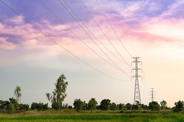 Torre de alta tensão distante na cena do sol de campo