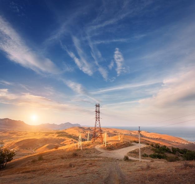Torre de alta tensão nas montanhas ao pôr do sol. sistema de pilão de eletricidade